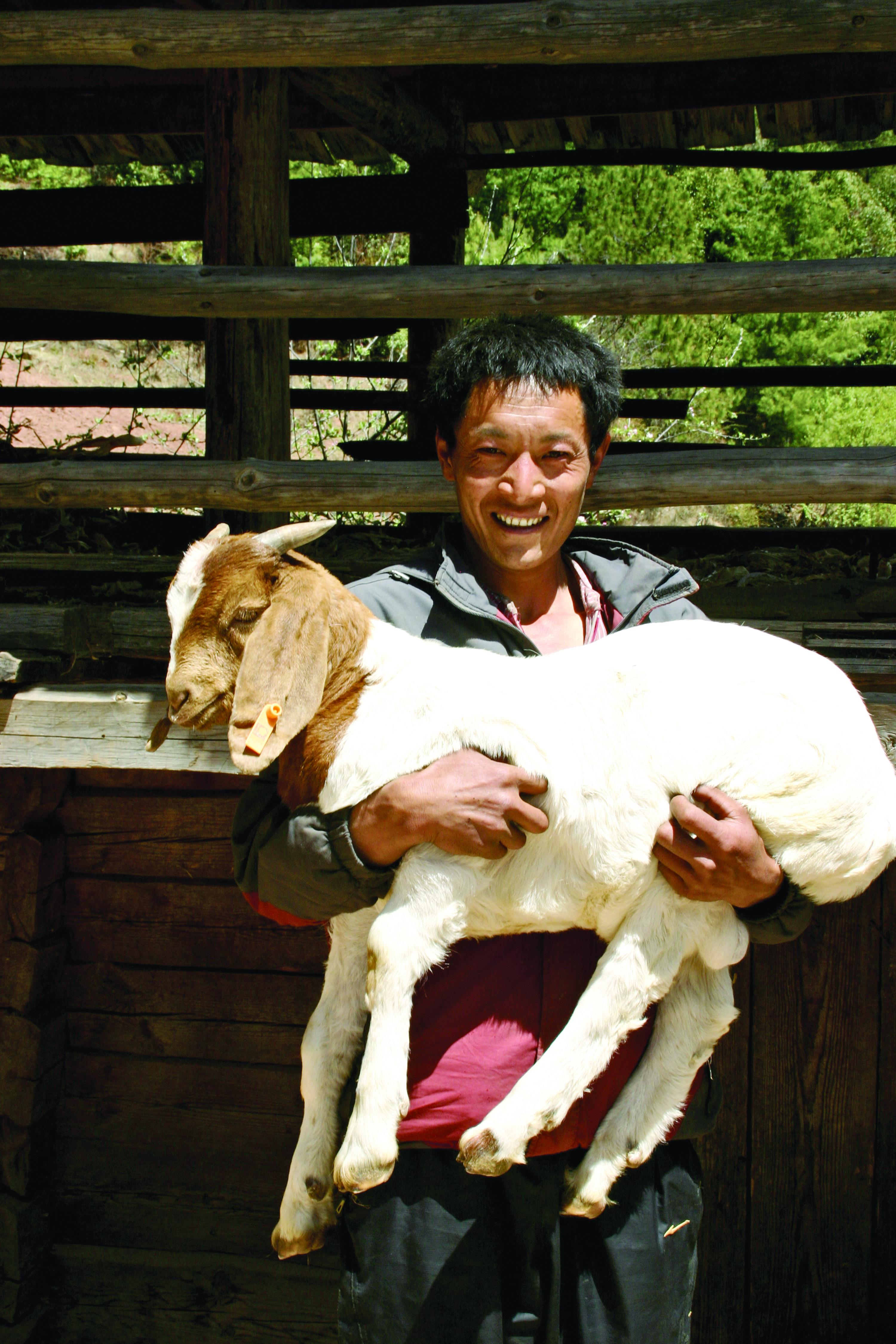 Smiling man with goat in his arms