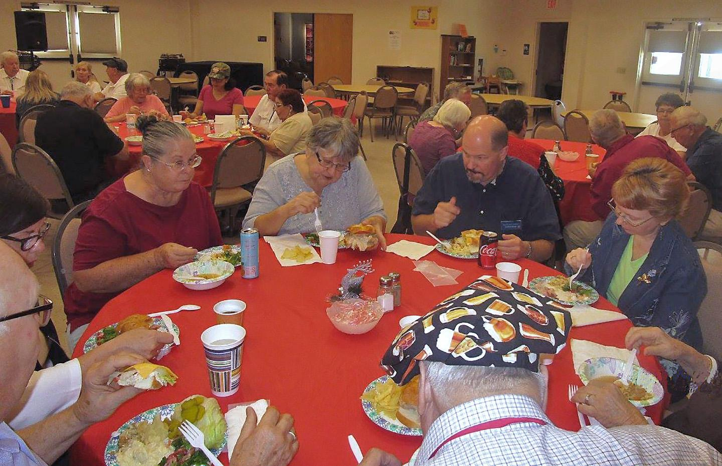 PrimeTimers gather around tables for laughs and food.